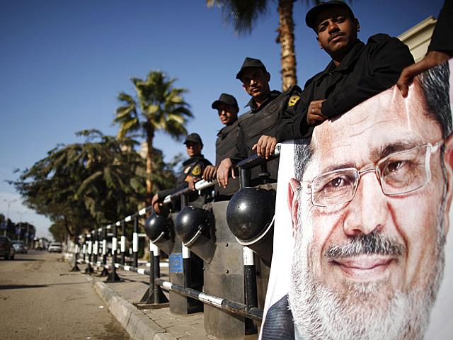 Policías alrededor del Tribunal Constitucional egipcio junto a un cartel de Mohamed Morsi. Fuente: Reuters