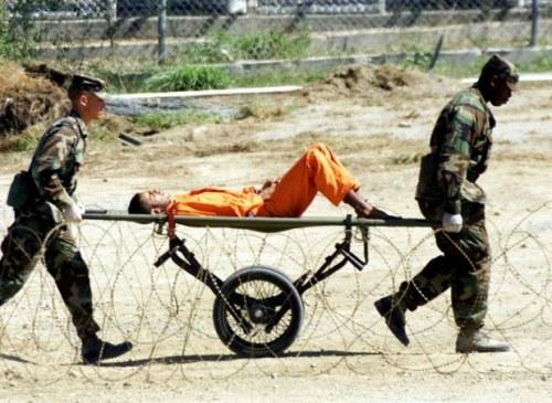 Un preso de Guantánamo acompañado por dos guardias. Fuente: http://www.vtv.gob.ve/articulos/2013/01/22/guantanamo-el-mensaje-del-sistema-ilegal-y-genocida-de-ee.uu-1371.html/guantanamo.jpg/@@images/2f54b8ad-8781-4c8c-ae3c-01ae9b4e5cb3.jpeg